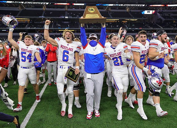 Westlake head coach Todd Dodge proudly hoists the state championship trophy amongst his players.