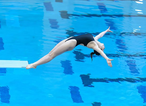 A female diver soars above the pool during the CHSAA 3A State Diving Championships in Colorado.