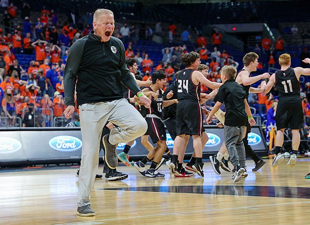 Texline (Texas) head coach Coby Beckner celebrates on the court with his players (background) after winning the  UIL Class 1A state championship game at the Alamodome in San Antonio.