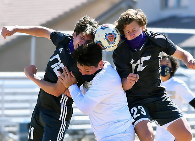 Two Northwest Christian (Ariz.) players battle a Parker player (middle) for a header.