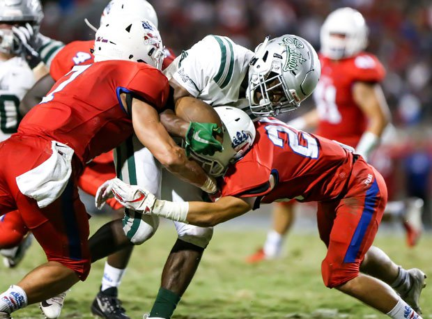 De La Salle senior Henry To'oto'o bulls his way through two would-be tacklers.