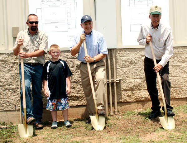 Bliss (center) helps to break ground for a new basketball arena at Allen Academy.