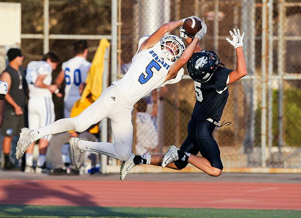 Burbank (Calif.) receiver Ben Burnham makes a leaping catch for a touchdown in front of Crescenta Valley defensive back Sam Kunz during a junior varsity contest.