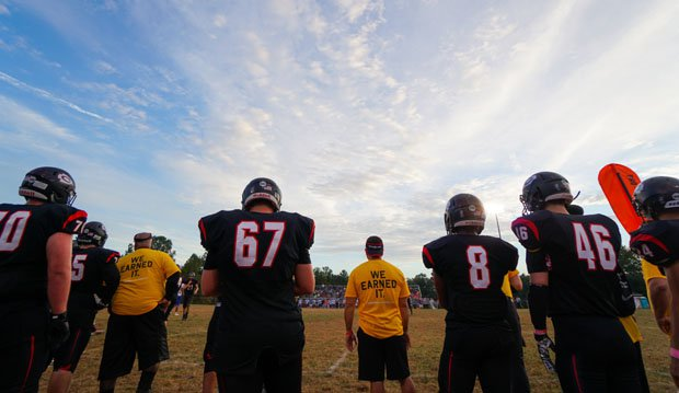 The Chopticon staff, donning their Touchdowns Against Cancer shirts, and players look on during the Leonardtown game.