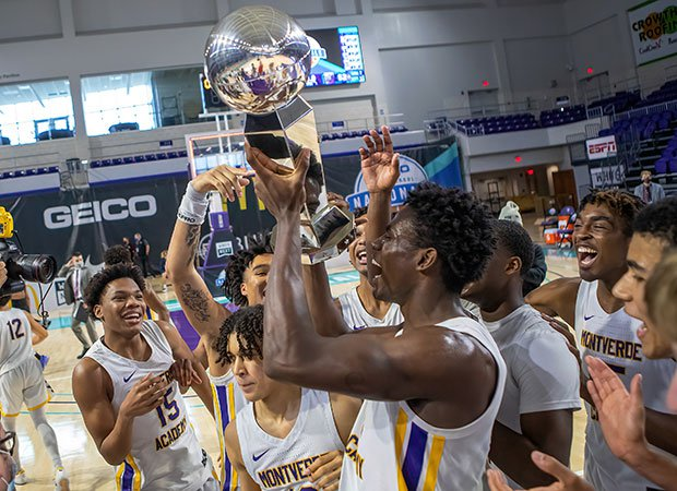 Jalen Duren proudly hoist the championship trophy while celebrating with teammates.