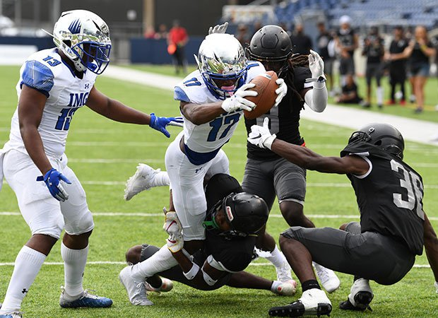 Receiver Carnell Tate dives into the end zone for one of his two touchdowns for IMG.