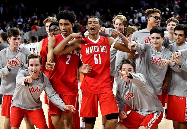 Mater Dei's Justice Sueing (2) and Harrison Butler (51) celebrate with teammates following their upset victory over Chino Hills on Friday night.