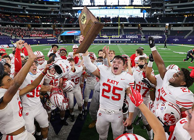 Katy (Texas) senior Shepherd Bowling proudly hoists the trophy among his celebrating teammates after winning the UIL 6A Division 2 state championship game over Cedar Hill at AT&T Stadium.