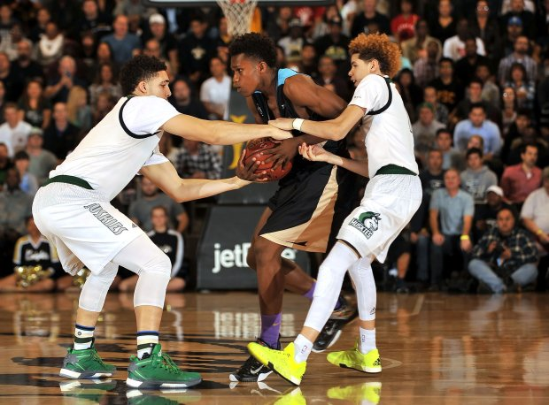 Brothers LiAngelo (left) and LaMelo Ball of Chino Hills tie up a Bishop Montgomery ballhandler in the first half.