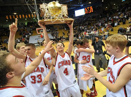 Chaparral's Josh Adams holds high the Class 5A basketball state championship trophy after its 69-67 overtime win against Arapahoe.