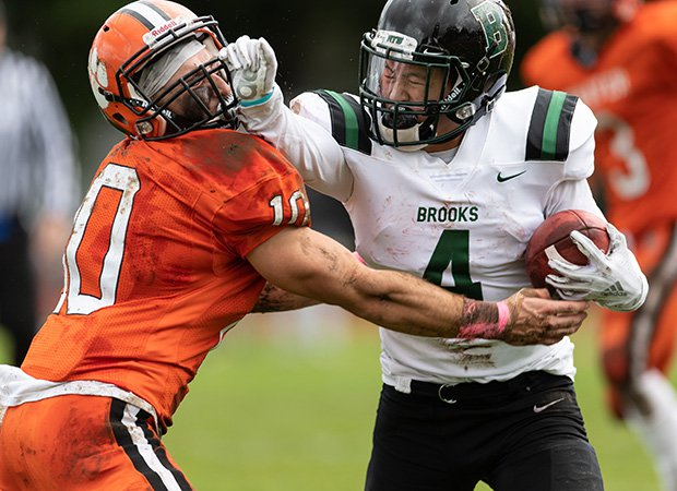 Running back Ben Gill of Brooks (Mass.) stiff-arms Thayer Academy's Jack Schneider.