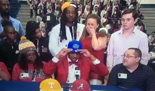 Jacob Copeland (center) tries on Florida cap, signaling his choice to the Gators, which didn't sit well with his mom (to his right).