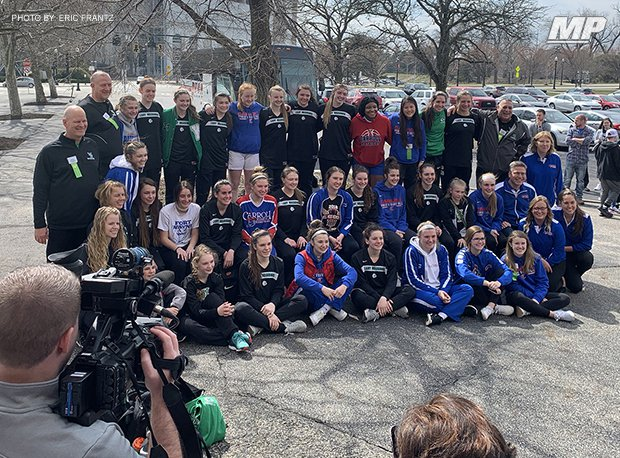 Basketball players and coaches from Carroll and West Branch high schools gather together for a photo outside St. John Arena after their Division II state semifinal was postponed.