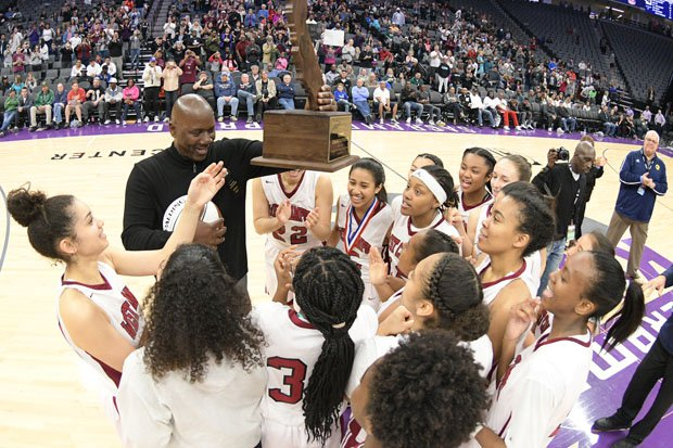 West Campus coach John Langston holds up his school's first state title.