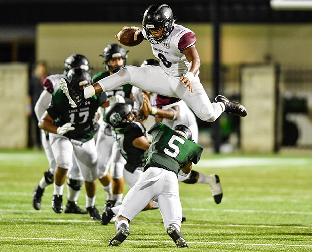 Mansfield Timberview (Texas) quarterback Jordan Davis hurdles Lake Ridge defender Addison McCarther.