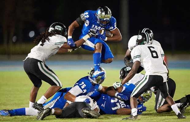 Noah Cain of IMG Academy leaps over a pile of players while attempting to elude several Miami Central defenders.
