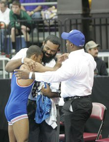 Trey Andrews gets congratulations from brother Tyrell Andrews, left, andfather Herman Andrews, right.