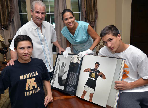 Biaggio Ali Walsh (right) with his brother, Nico, along with their father, Bob Walsh, and mother, Rasheda Ali-Walsh, look through a book highlighting the boxing career and life of family patriarch Muhammad Ali. Biaggio is a star freshman running back for Bishop Gorman in Las Vegas.