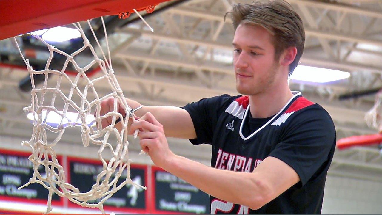 Connor Christensen cutting down the net in March 13 ceremony at Eden Prairie.
