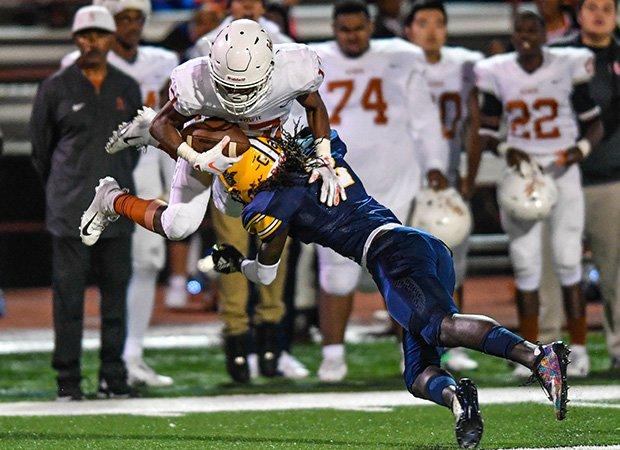 Lamar (Texas) cornerback Deshawn Gaddie launches Bowie receiver Jordon Joyner.