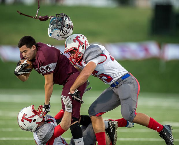 A Northbrook player's helmet is sent soaring while two Tomball defenders tackle him during an October game in Texas.