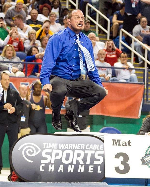 A Hickory Ridge (N.C.) coach leaps while celebrating a victory by his wrestler in the finals of the NCHSAA 3A state championships.