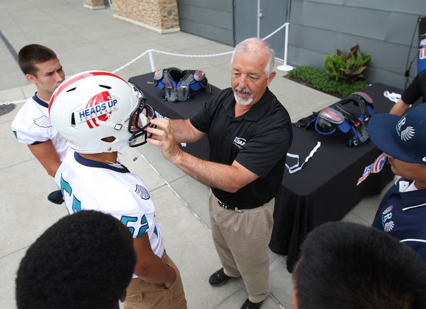 WIAA assistant executive director John Miller assists in a Heads Up Football demonstration at the USAFootball/MaxPreps High School Football Media Day in Seattle.