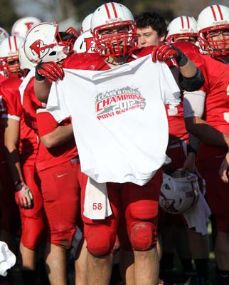 Sean Struncius holds up a championship T-shirt following his team's win on Thanksgiving Day.