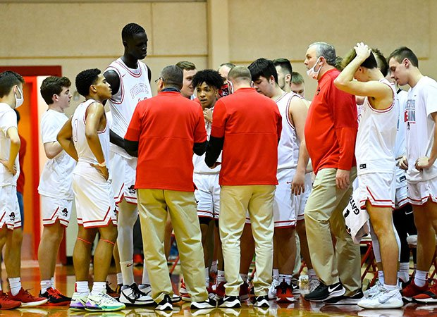 Bol looks down from above on his teammates during a time out.
