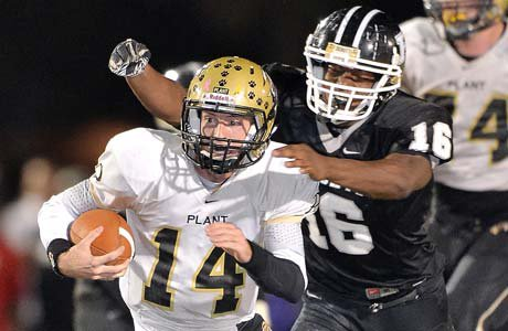 Plant quarterback Aaron Banks attempts to elude Justin Madison of Robinson.
