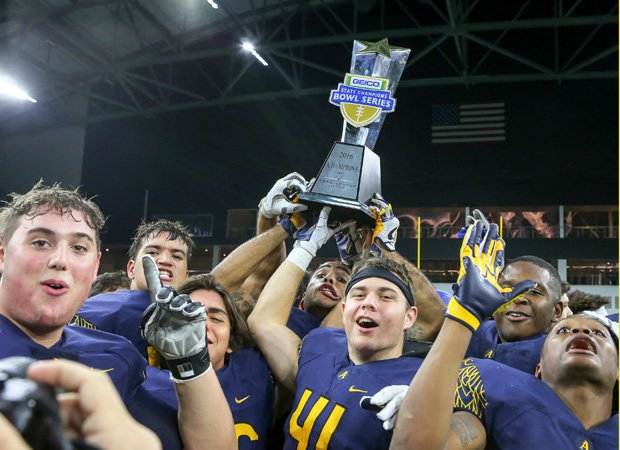 St. Thomas Aquinas (Fla.) players hoist the Geico State Champions Bowl Series trophy following their victory over Bingham (Utah) at The Star in Texas.