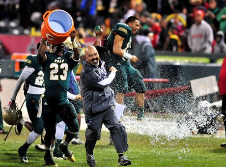 Running back Gerard Wicks douses coach Raul Lara with an icy bucket of celebration water after Long Beach Poly continued its postseason blitz with a triumph over Mater Dei in the Pac-5 title game.