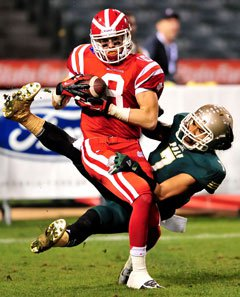 Mater Dei receiver Nikolas Little makes a  touchdown catch in front of a Poly defender.