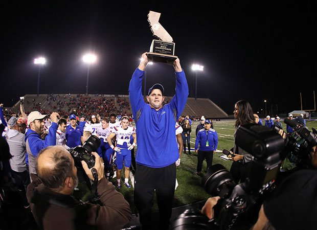 Kris Richardson holds up his fourth CIF State championship trophy on Dec. 14 at Cerritos College following a 21-14 overtime win over Cathedral Catholic.