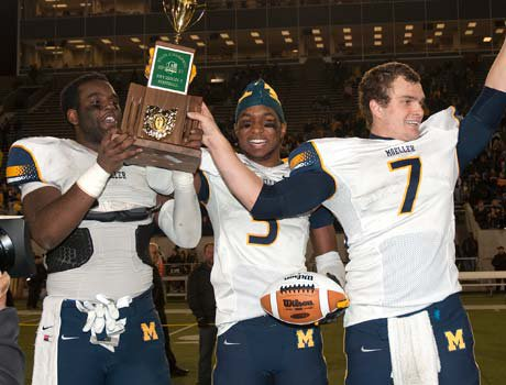 Moeller players raise the trophy while celebrating their victory on Saturday.