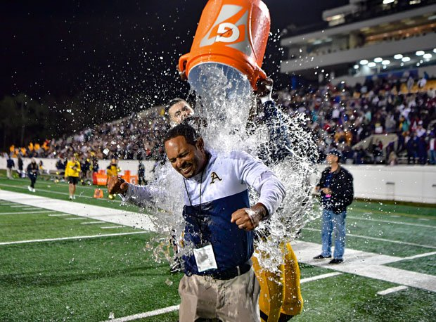 Aquinas coach Roger Harriott enjoys Gatorade bath.