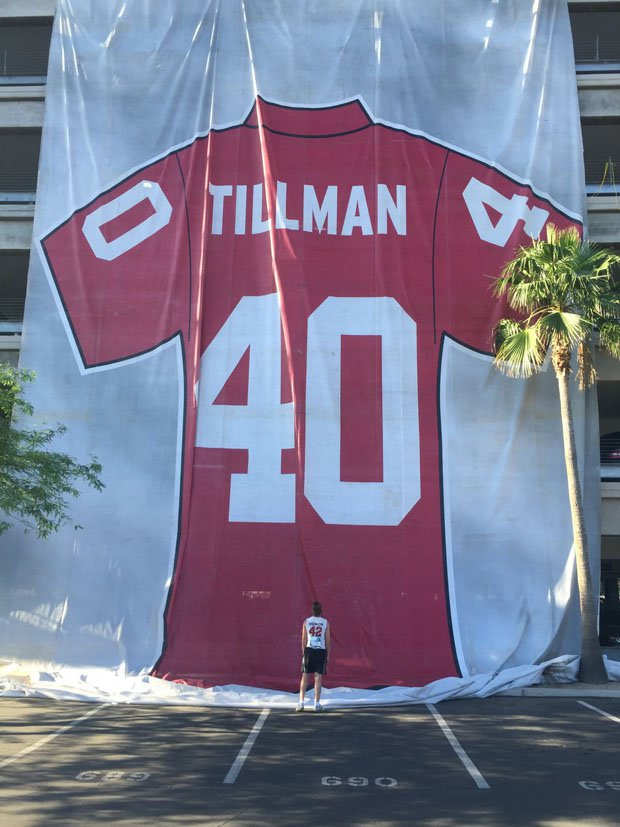 "Adam Garwood looking up at a gigantic Pat Tillman jersey before an annual 4.2-mile run in Tempe (Ariz.) put on by the Pat Tillman Foundation. ""Pat's Run"" is the signature fundraiser for the foundation's scholarship program, this year scheduled April 24 to be run virtually."