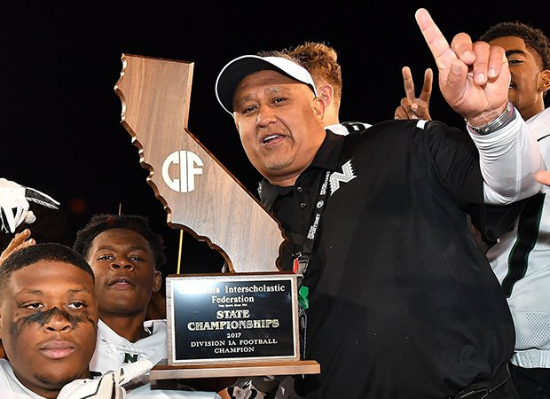 Head coach Manuel Douglas proudly displays the championship trophy following his team's victory in last year's CIF Division 1-A state title game.
