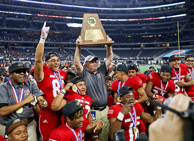 North Shore head coach Jon Kay proudly hoists the trophy as his players celebrate a second straight Texas 6A Division 1 football championship before 47,818 fans at AT&T Stadium.