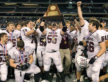 East Bernard players celebrate winning the Texas Class 2A Division II state championship by hoisting the trophy.