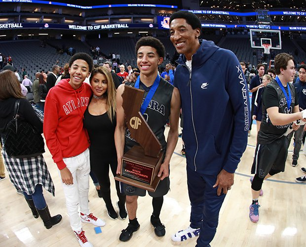 Scotty Pippen takes a family photo with the trophy.