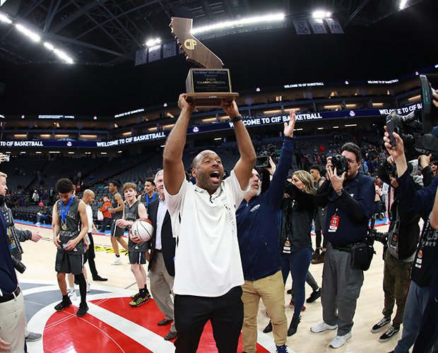 Sierra Canyon coach Andre Chevailer proudly hoist the state championship trophy.