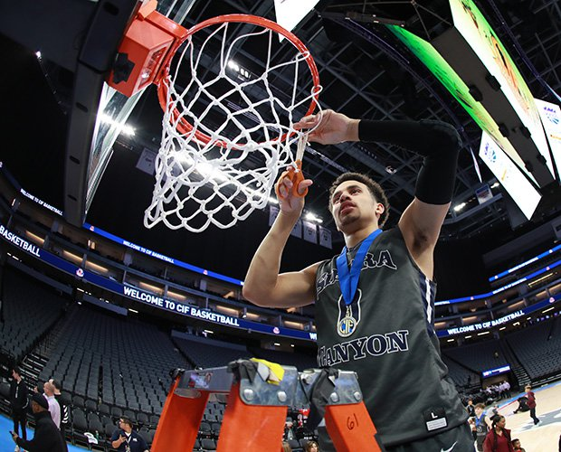 Sierra Canyon's Duane Washington cuts off a piece of the net at Golden 1 Center in Sacramento.